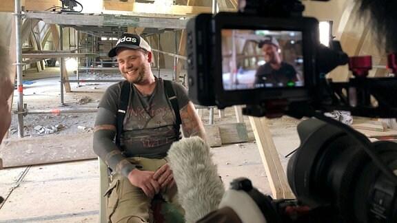 Steinmetz Matthias wird in der St. Nikolaikirche in Quedlinburg vom Kamerateam interviewt.