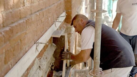 Stuckateursmeister Siggi zieht mit dem selbstgebauten Schlitten neue Gesimse aus Sand und Kalk.