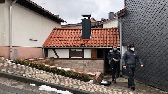 Zwei Männer vor einem kleinen Fachwerkhaus.