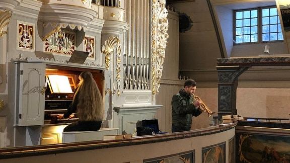 Eine Organistin spielt auf einer aufwendig dekorierten, historischen Kirchenorgel, während sie von einem Trompeter begleitet wird.