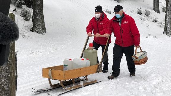 Zwei Männer schieben einen Schlitten, auf dem sich einige Kanister befinden, durch einen verschneiten Wald.