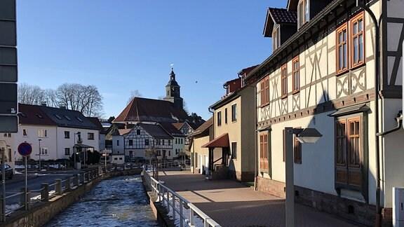 Ein schmaler Fluss fließt entlang eines Wegs, an dem Fachwerkhäuser stehen. Im Hintergrund ist eine kleine Kirche zu sehen.