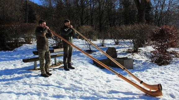 Zwei Männer stehen in einem verschneiten Wald und spielen Alphörner.