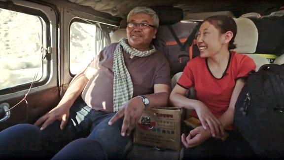 Ein Mann und eine Frau sitzen in einem Bus.