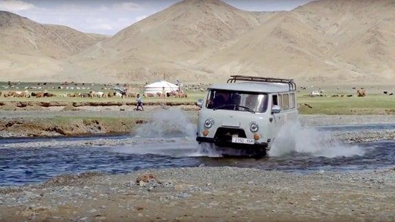 Ein alter Geländewagen fährt durch einen Fluss.