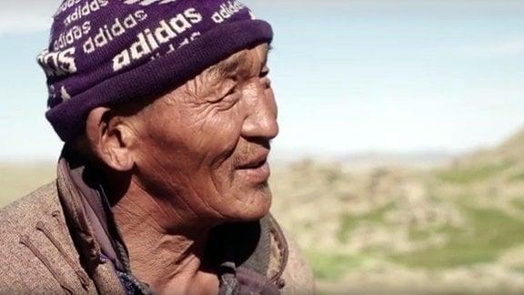 Ein alter Mann schaut vor einer weiten Landschaft nach rechts.