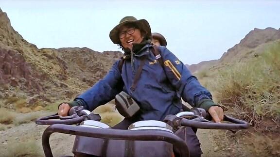 Ein Mann fährt auf einem Quad durch eine hügelige Landschaft.