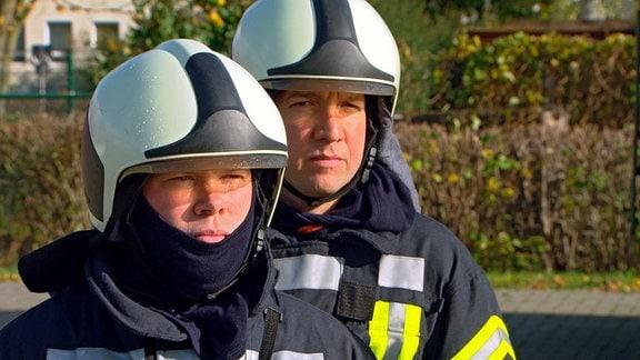 Die Feuerwehrschüler Sebastian Liebe (li) und Reinhard Stube warten während einer Übung auf Befehle.
