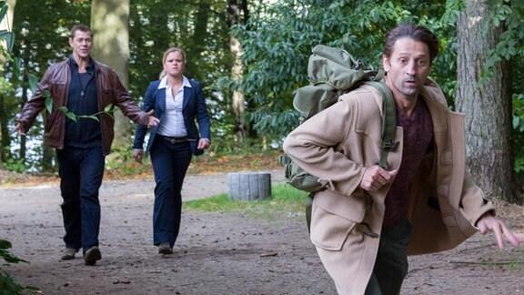 Finn Kiesewetter (Sven Martinek, l.) und Sandra Schwartenbeck (Marie-Luise Schramm, M.) treffen im Wald auf Frank Clasen (Andreas Patton, r.), der vor ihnen davonläuft.