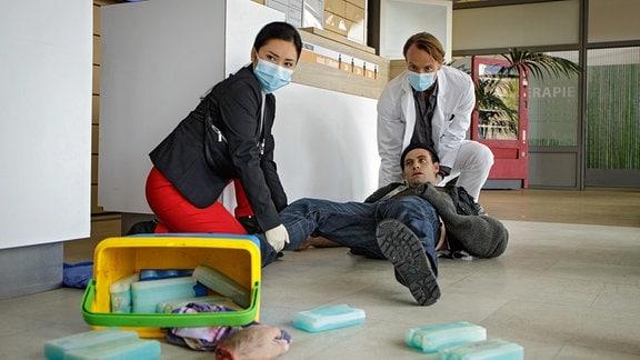 Als Dr. Lilly Phan (Mai Duong Kieu, li.) morgens die Sachsenklinik betritt, bricht gerade ein Mann (Jonathan Müller, liegend) an der Rezeption zusammen. Aus einer Kühlbox fällt sein Unterarm. Dr. Martin Stein (Bernhard Bettermann; re.) ist sofort zur Stelle.