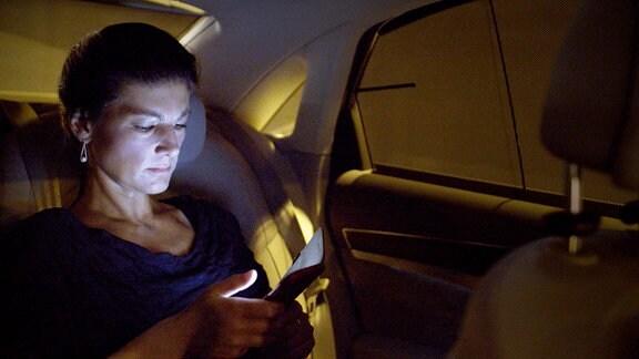 Sahra Wagenknecht, bei Nacht in einem PkW sitzend, schaut auf ihr Handy.