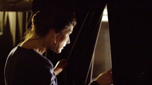 Sahra Wagenknecht blickt durch einen leicht geöffneten Vorhang