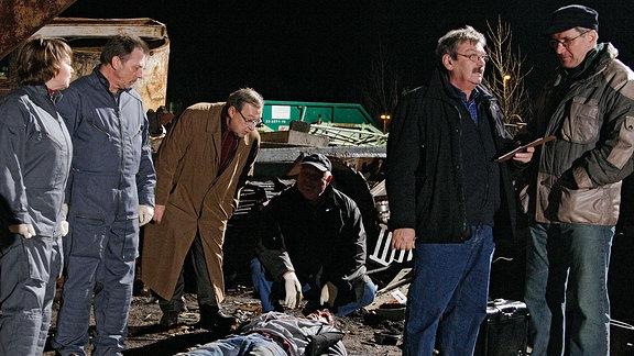 Matthias Noacks Leiche (Nils Nelleßen) wurde erschlagen auf einem Schrottplatz gefunden. Schmücke (Jaecki Schwarz, 3. von links ) und Schneider (Wolfgang Winkler, 2. von rechts) holen erste Informationen ein.