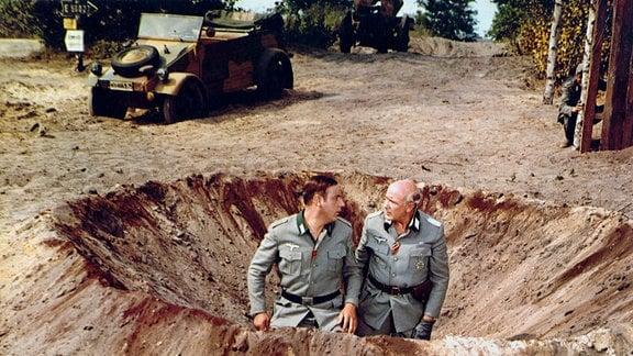 """Major Steckbeck (Kurt Jung-Alsen, r.) lässt den unerfahrenen Soldaten Kurt """"Kutte"""" Hartung (Manfred Krug) einen Blindgänger entschärfen."""