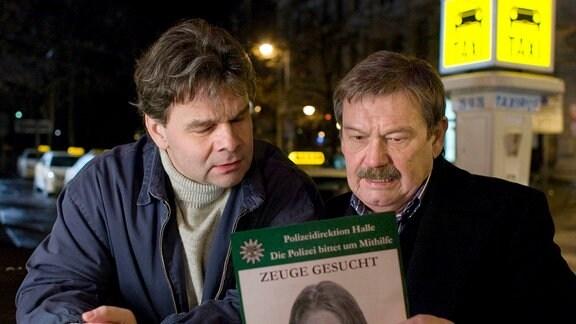 Schneider (Wolfgang Winkler, rechts) verteilt am Imbiss Phantombilder unter den Taxifahrern.