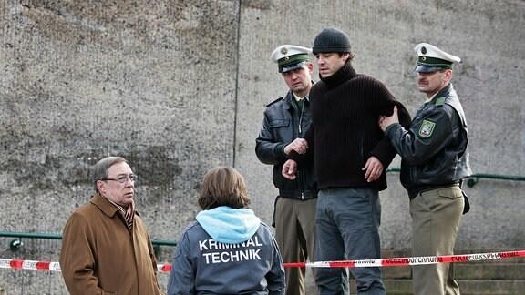 Taxiunternehmer Georg Sendler (Tobias Oertel, oben Mitte) wird an der Absperrung von Beamten festgehalten. Schmücke (Jaecki Schwarz, links) kommt dazu.