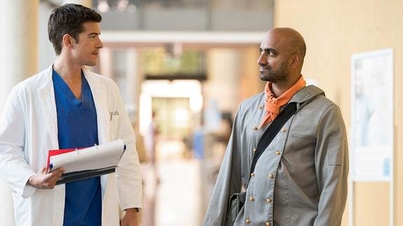 Ben (Philipp Danne, l.) möchte seinen Patienten Anand Sangh (Murali Perumal, r.) davon überzeugen, die verletzte Hand genauer untersuchen zu lassen.