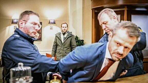 Florian (Arne Löber, h.M.) stellt sich vor, wie Erik (Sven Waasner, r.) von der Polizei (Komparsen) festgenommen wird.