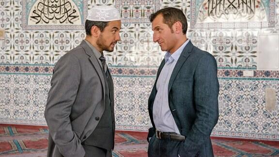 Der Imam (Ercan Karacayli) tadelt Zeki Demirbilek (Tim Seyfi) dafür, dass er Schweinebraten gegessen hat.