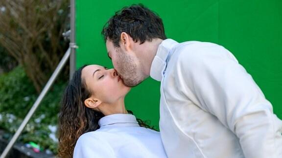 Am Ende der Dreharbeiten wird Vanessa (Jeannine Gaspár,  l.) doch noch von Georg (Robert Herrmanns, r.) geküsst.