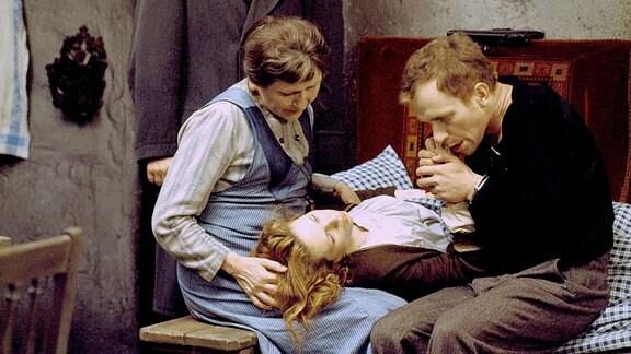 Mutter Fent (Ursula Braun) stützt den Kopf ihrer Tochter Hete (Renate Krößner), Dr. Möller (Heinz Behrens, stehend) und Hetes Verlobter Paul (Hermann Beyer) sehen bestürzt zu.
