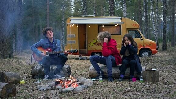 Aksel (Jakob Dyrud) spielt am Lagerfeuer einen schrägen Song für Grim (Tage Hogness, Mi.) und Thilda (Tiril Marie Høistad Berger).