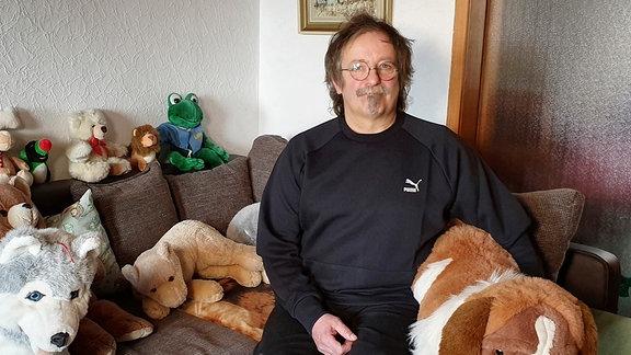 Lokführer Thomas Just auf seinem Sofa voller Kuscheltiere