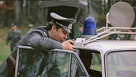 Volkspolizist gibt Funkmeldung am Polizei-Lada durch.