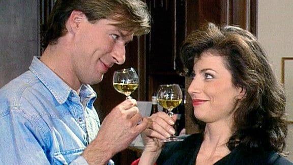 Kathrin (Marijam Agischewa) und Jens (Rolf Lindermann) stoßen mit einem Gläschen edlen Wein an.