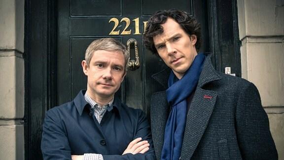 Zwei jüngere Herren stehen vor einer Tür.