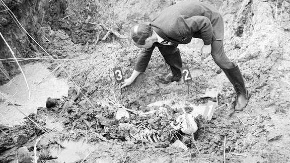 Ein Skelet wird von einem Gerichtsmediziner betrachtet.