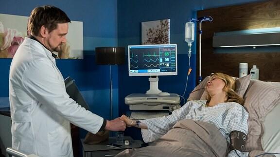 Claudia (Tina Amon Amonsen, r.)liegt in einem Krankenhausbett.  Neben ihr steht Marc (Christian Beermann, l.), der ihre Hand hält und einen weißen Kitteö trägt.
