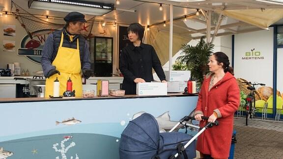 Ben (Hakim Michael Meziani, l.) und Ellen (Yun Huang, M.) zeigen sich vor Tina (Katja Frenzel, r.) optimistisch, dass ihre Kochboxen bei den Kunden gut ankommen.