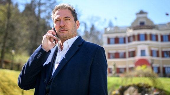 """Christoph (Dieter Bach)telefoniert. Im Hintergrund: Der """"Fürstenhof""""."""