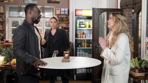 Amelie (Lara-Isabelle Rentinck, l.) bittet Hendrik (Jerry Kwarteng, r.) vor Britta (Jelena Mitschke, M.), sie als Begleitung zu dem Charity-Event einzuschleusen.