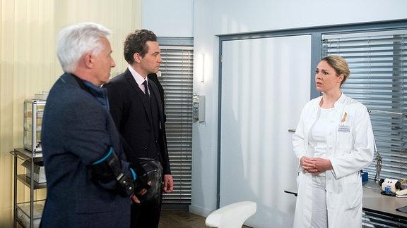 Britta (Jelena Mitschke, r.) ist vor den Kopf gestoßen, als Thomas (Gerry Hungbauer, l. mit Leander Lichti, M.) damit droht, die Klinik nun doch verklagen zu wollen.