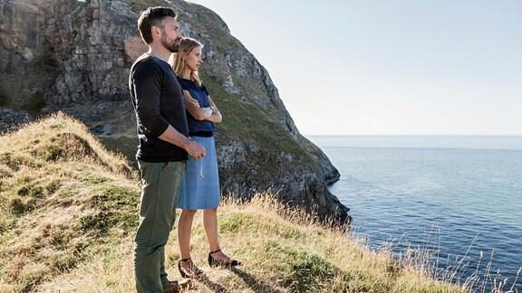 Ein Herr und eine Dame blicken von eine Klippe ins Meer