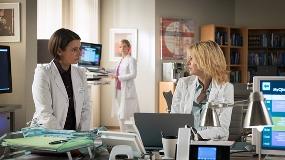 Dr. Maria Weber (Annett Renneberg, li.)  mit  Dr. Ina Schulte (Isabell Gerschke, re.) im Gespräch. Dr. Kathrin Globisch (Andrea Kathrin Loewig, hinten) wird zufällig Zeugin dieses Gesprächs.