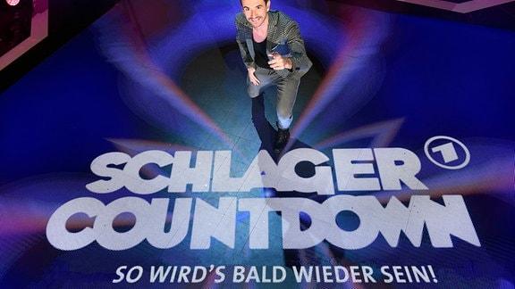 """Florian Silbereisen steht auf der Bühne und lacht in die Kamera. Auf dem Bühnenboden steht """"Schlagercountdown - So wird's bald wieder sein!"""""""