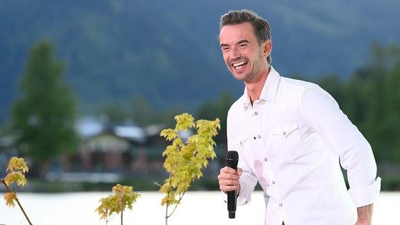 Ein lachender Florian Silbereisen im weißen Hemd vorm Bergpanorama