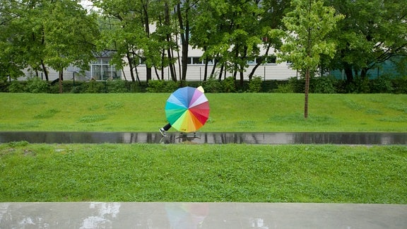 Eine Person bewegt sich hinter einem bunten Schirm.