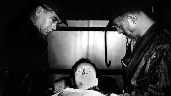 """Ein Bildausschnitt aus dem Film """"Sonnensucher"""", in der drei Männer zu sehen sind. In der Mitte liegt einer von ihnen mit geschlossenen Augen, die anderen beiden stehen zu seiner Rechten und Linken."""