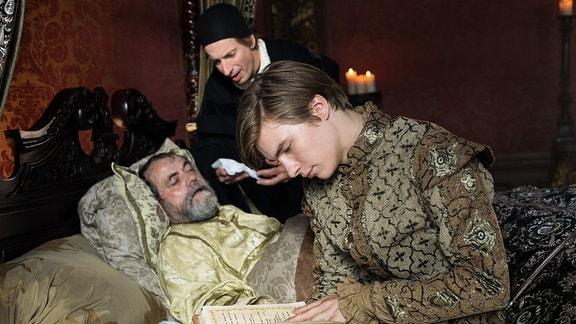 König Ansgar (Matthias Brenner) liegt im Bett. Sein Leibarzt (Ingolf Lück, M) beugt sich über ihn, während Prinz Lennard (Gustav Schmidt, r)  ein Buch studiert.
