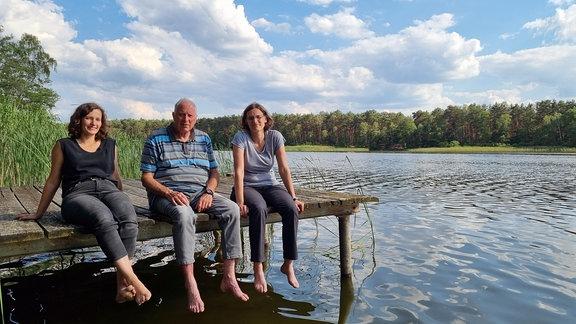 (V.l.n.r.) Susi, Achim und Beate Schneider sitzen auf einem Steg am Frauensee.