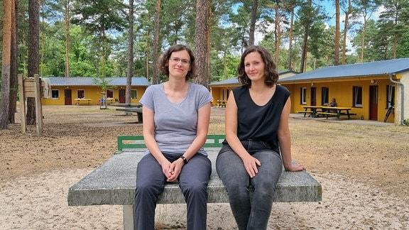 Beate (l.) und Susi Schneider sitzen vor einer Bungalowsiedlung am Frauensee.