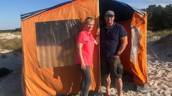 Christiane und Mathias Reinäcker stehen vor einem Zelt am Prerower Strand.