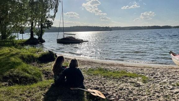 Madeleine (l.) und Jenny sitzen am Ufer der Müritz und schauen aufs Wasser.