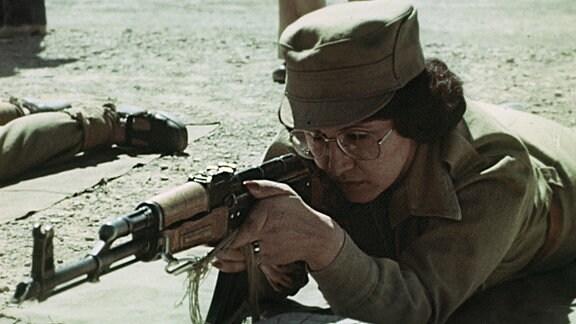 Eine afghanische Frau in Militäruniform bei Schießübung, Afghanistan 1980.