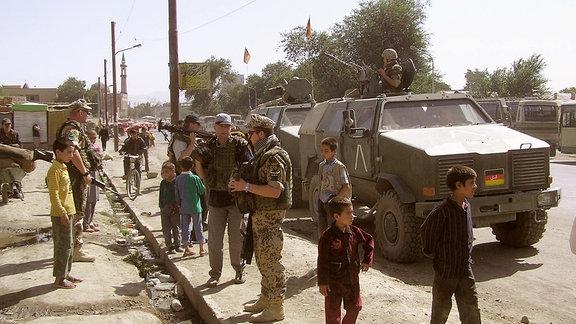Bundeswehrsoldaten zwischen afghanischen Menschen