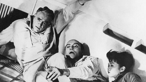 (v. l. n. r.): Oldrich Lukes (Hawling, amerikanischer Atomphysiker), Ignacy Nachowski (Saltyk, polnischer Chefingenieur) und Yoko Tani (Sumiko, japanische Ärztin).